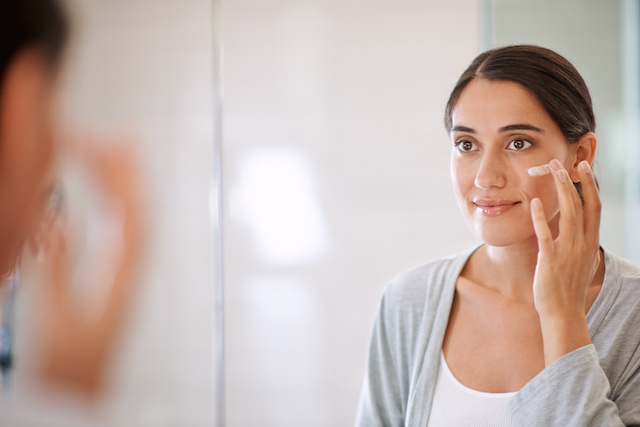 Woman applying NEUTROGENA® moisturizer to face