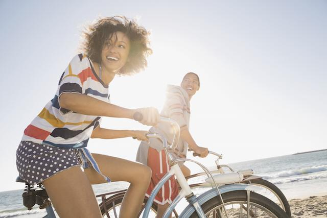 A young woman and man biking by the beach in the sun