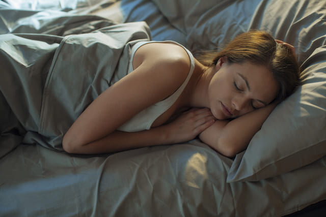 Woman sleeping in bed with NEUTROGENA® anti-aging nightime skin care on her face