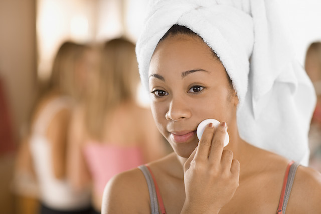 Woman removing makeup with NEUTROGENA® makeup remover & a cotton pad