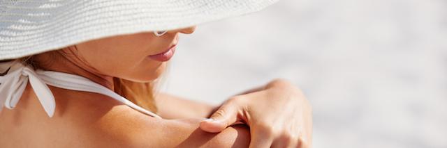 Woman applying NEUTROGENA® sunscreen to back