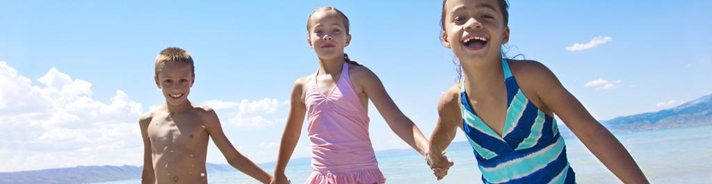 Kids playing on beach and wearing NEUTROGENA® kids sunscreen