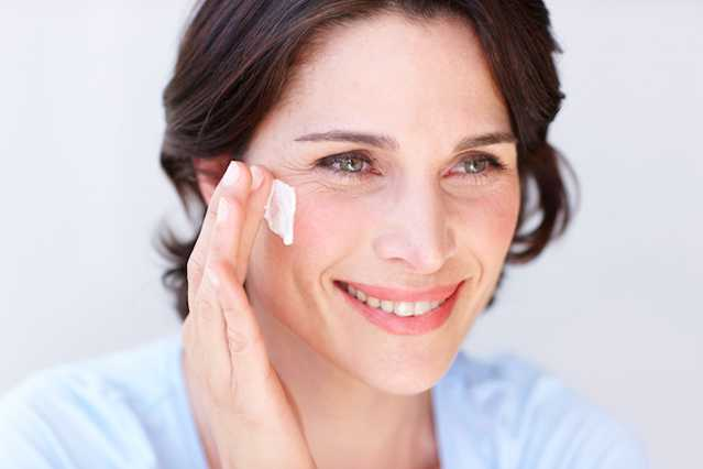 Woman applying NEUTROGENA® moisturizer to face with a cotton pad