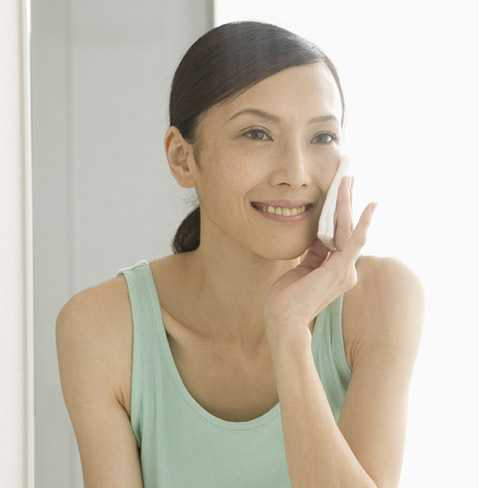 Smiling woman applying NEUTROGENA® products with a cotton pad, for anti-aging purposes.