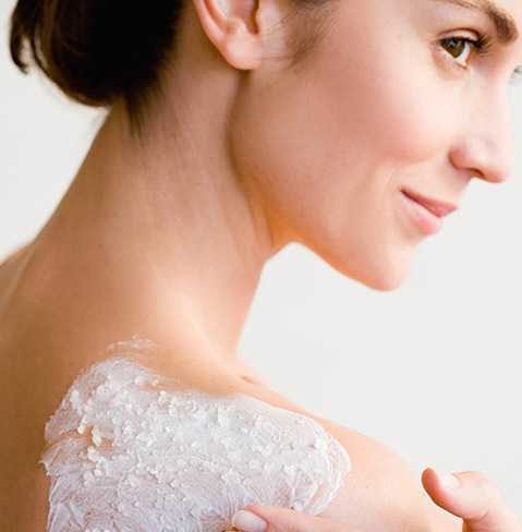 Woman lathering NEUTROGENA® body scrub on her shoulder.