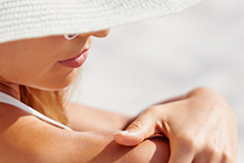 Woman applying NEUTROGENA® sunscreen to back